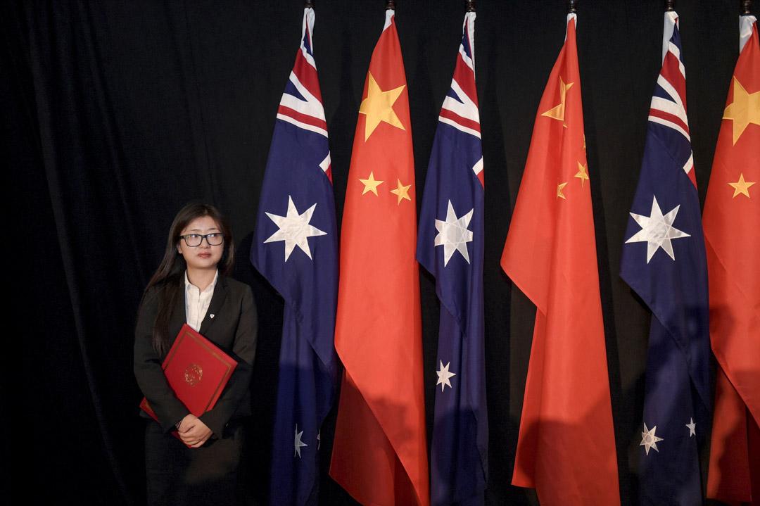 2015年6月17日,澳洲一個中澳官兵的簽字儀式上,一名拿著《自由貿易協定》副本的職員站在中澳國旗旁邊。