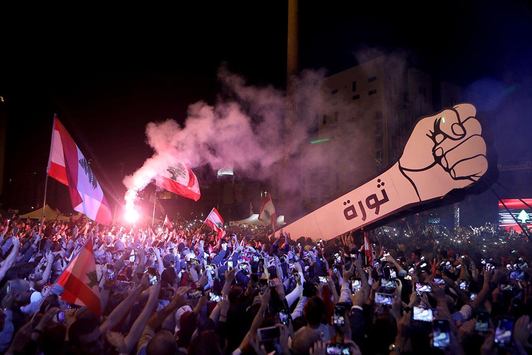 2019年11月22日,黎巴嫩首都貝魯特,示威者舉起一個寫著「革命」的巨型拳頭標語。該日是黎巴嫩第76年自治紀念日,成千上萬的群眾在街上狂歡遊行,他們稱這不是僵硬的閱兵歡呼而是在慶祝「真正的獨立」。