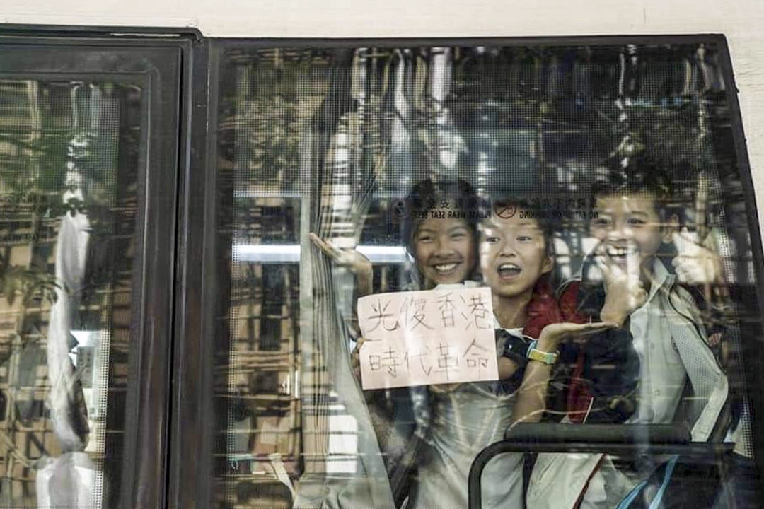 11月11日網上流傳的一幀照片,被困小巴車廂的孩子在車窗展示寫上「光復香港時代革命」的紙張。