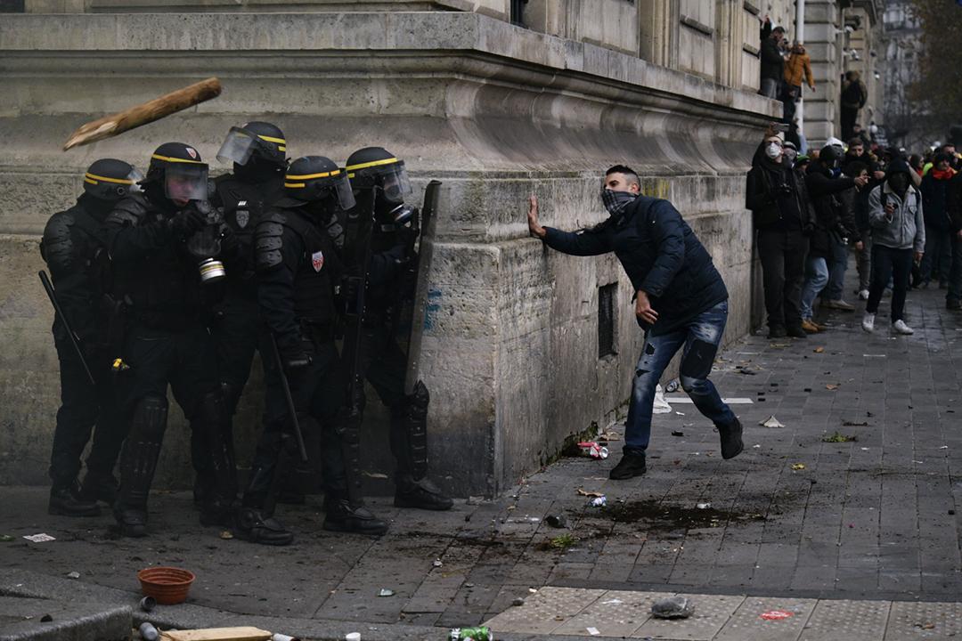2019年12月5日在法國巴黎,一名示威者與數名防暴警員分別處於建築物轉角處的兩側。 攝:Julien Mattia / Anadolu Agency via Getty Images