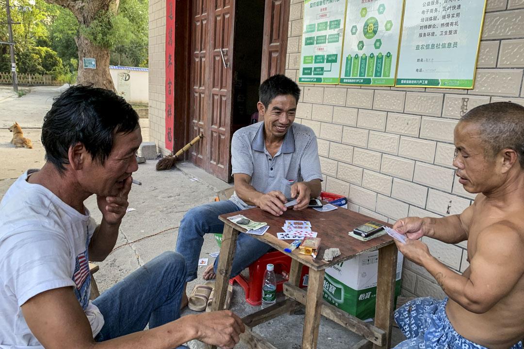 貧困戶楊華與村民玩撲克牌。