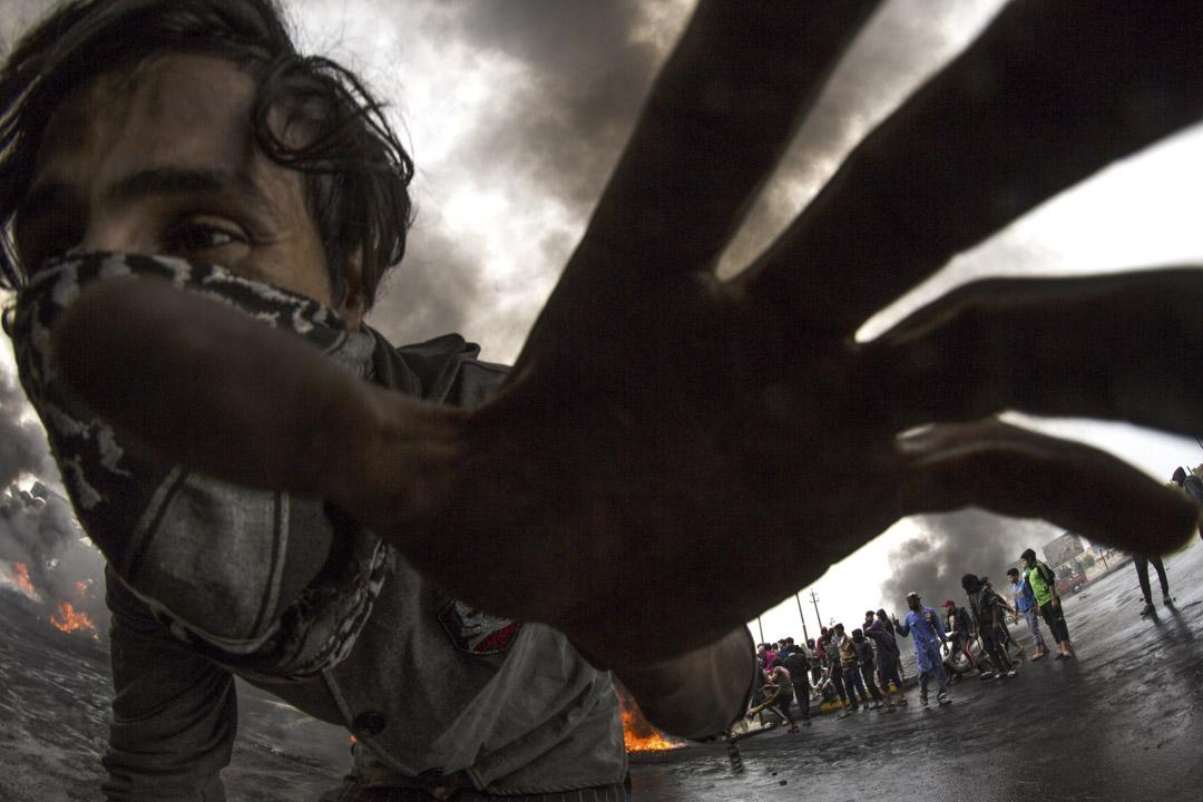 2019年11月25日,伊拉克南部,在反政府示威中,一名伊拉克示威者在試圖逃跑,其他的示威者在燒輪胎製造路障。自10月以來,示威者要求政府結束腐敗,進行改革增加就業和改善公共服務,政府安全部隊開槍鎮壓。