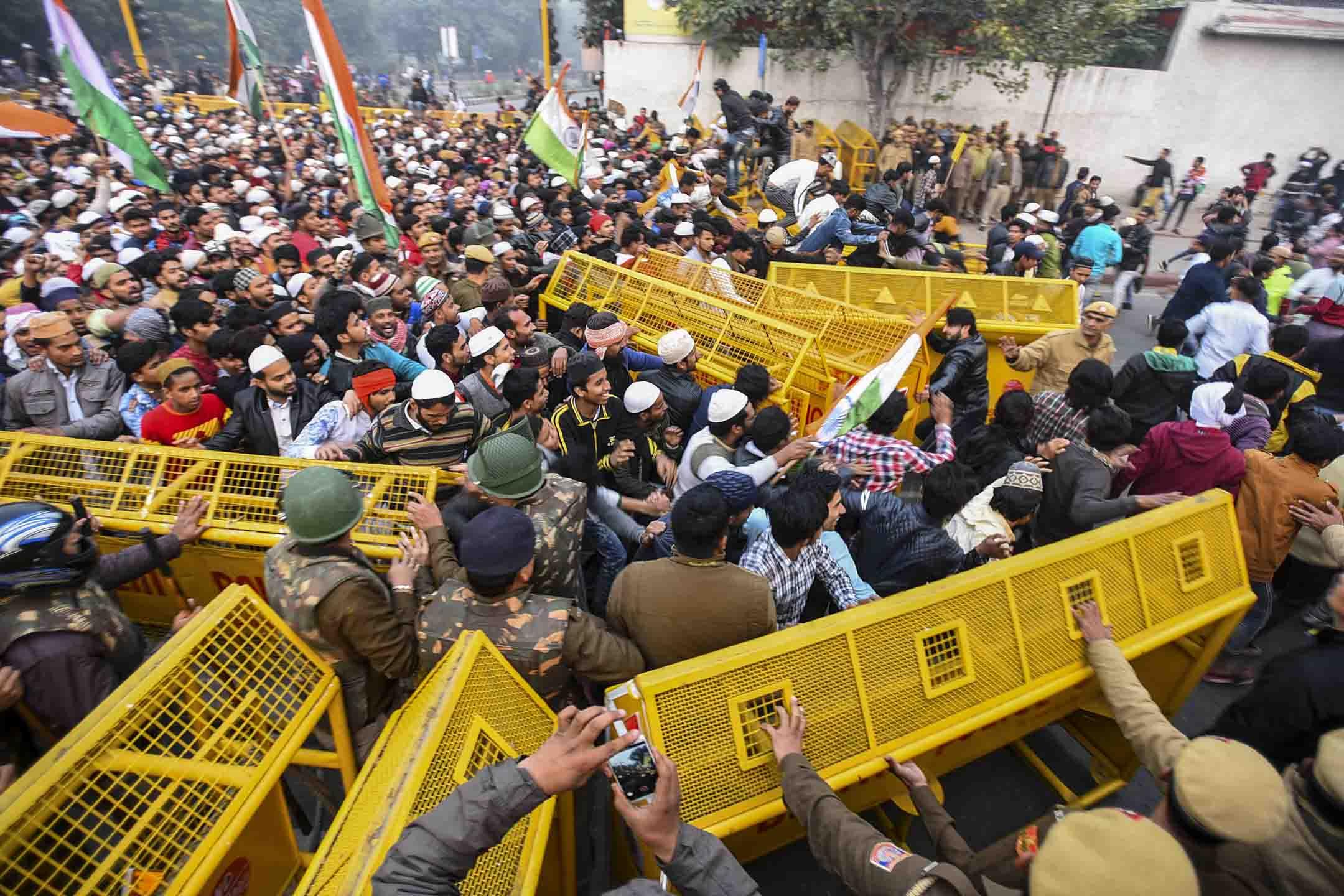 2019年12月20日,印度新德里舉行的反對《公民身份法》修正案的抗議活動中,示威者越過警察路障。  攝:Raj K Raj/Hindustan Times via Getty Images