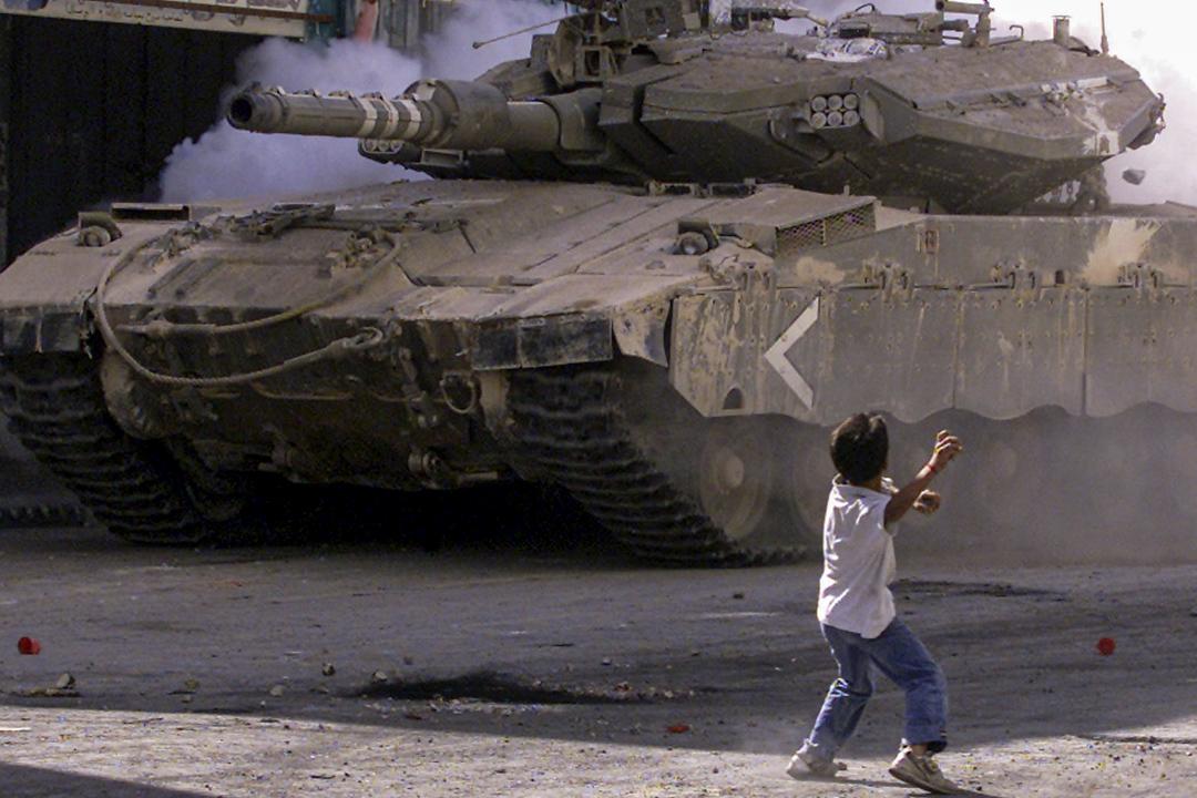 2003年10月11日,一個巴勒斯坦男孩向以色列軍隊的坦克投擲石塊。