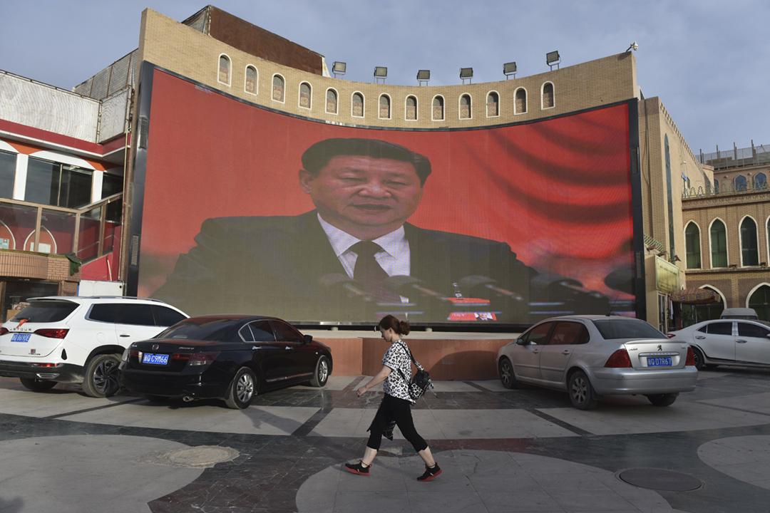 2019年6月4日在新疆喀什,一名女士經過幅大型屏幕,屏幕正播放中國國家主席習近平發表講話。 攝:Greg Baker / AFP via Getty Images