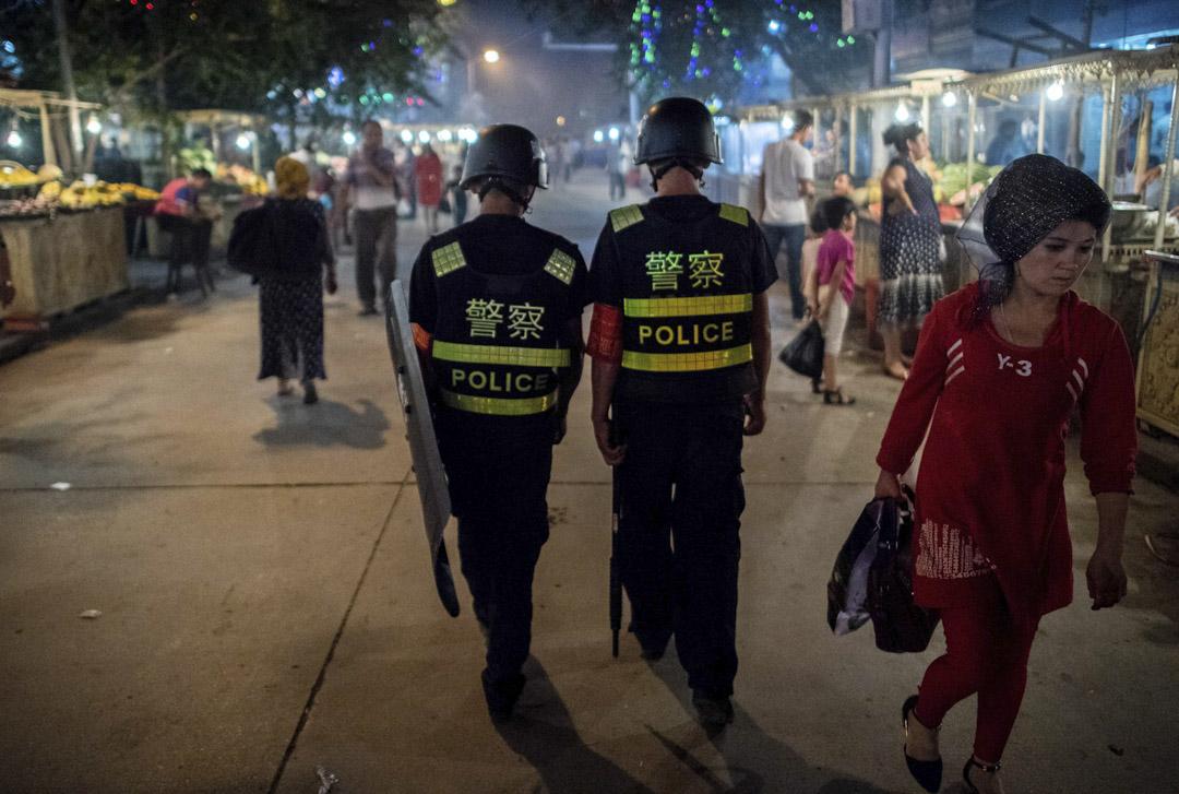 2017年6月25日,在開齋節假期的前一天,警察在中國新疆維吾爾自治區喀什市清真寺附近的夜市裡巡邏。