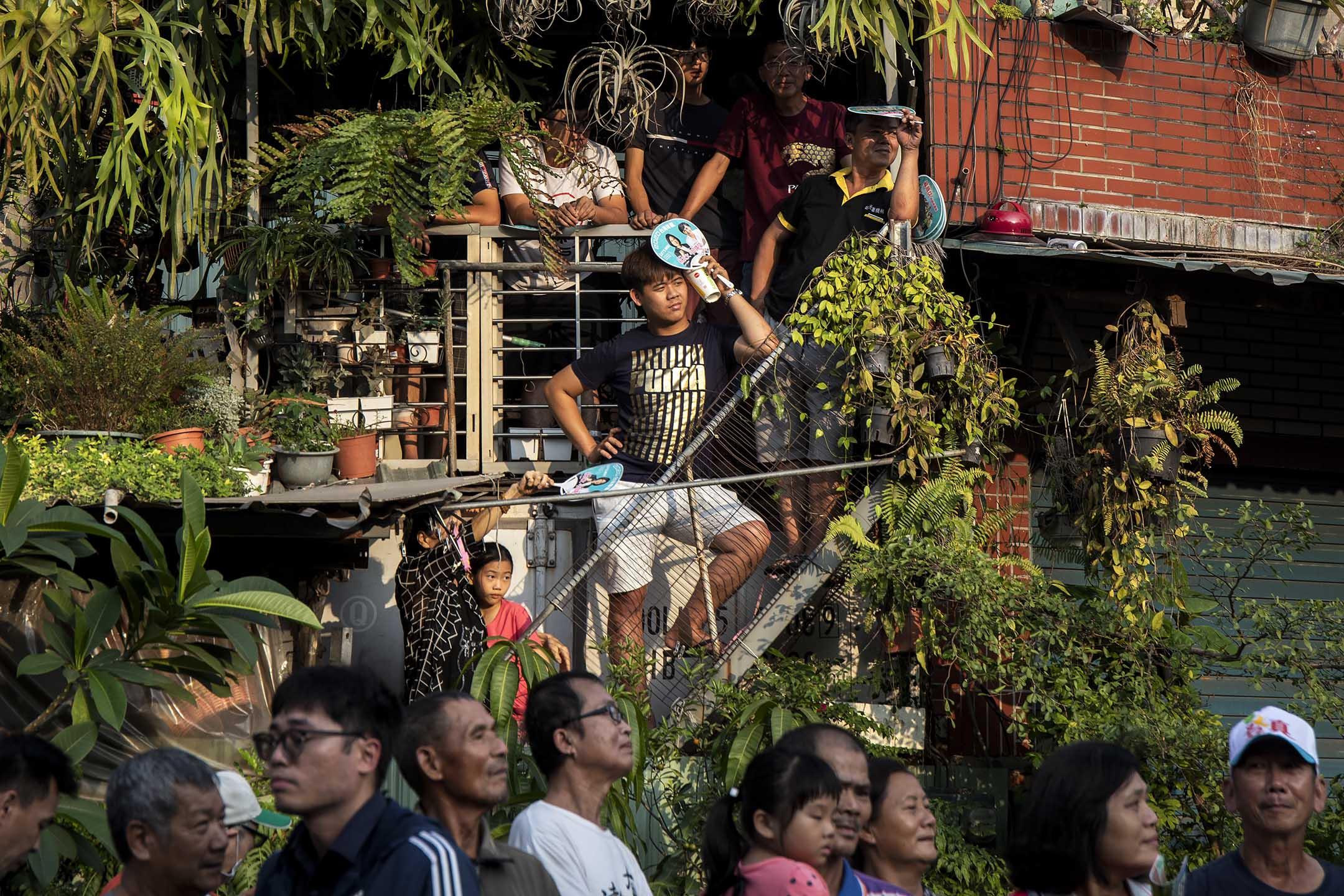 2019年11月4日,蔡英文在高雄宮廟參香期間,居民在家外拿著宣傳品遠觀。 攝:陳焯煇/端傳媒