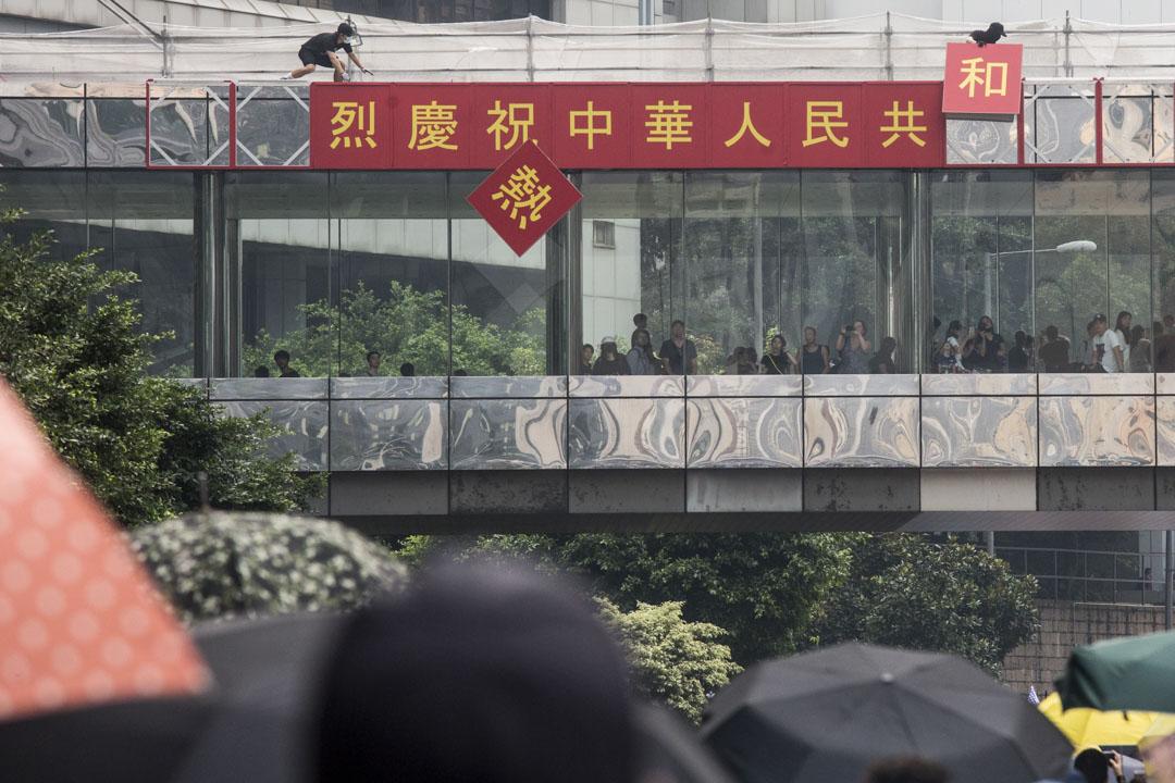 2019年9月29日,示威者於遊行期間拆去天橋上慶祝國慶的標語。 攝:林振東/端傳媒