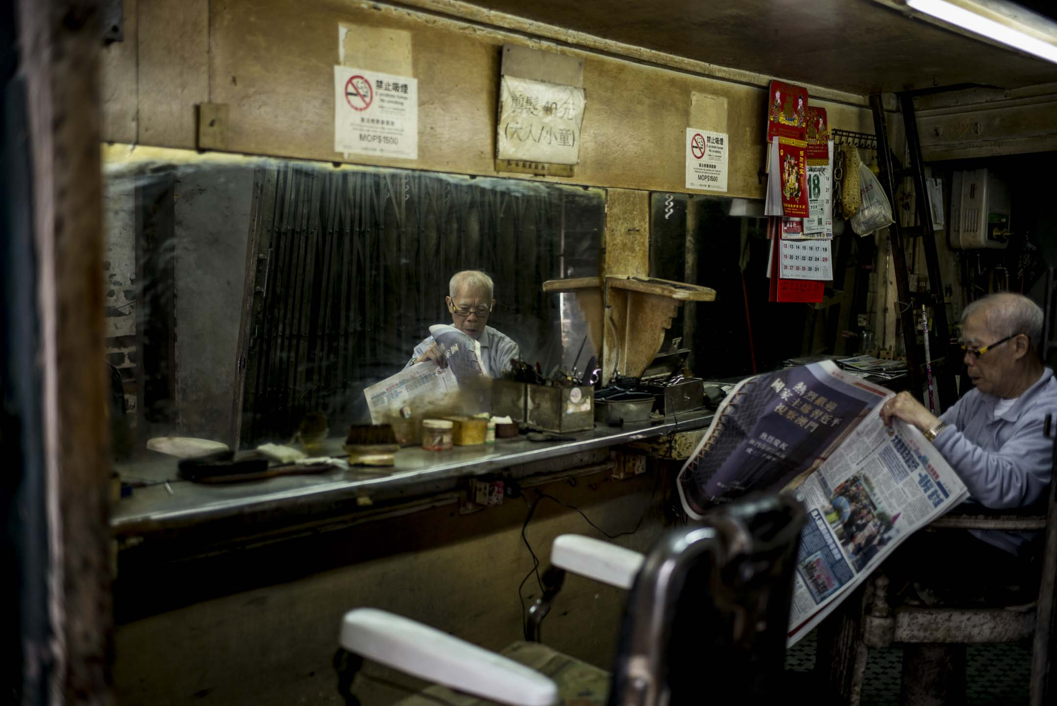2019年12月18日,澳門一名在後巷營業的理髮師,等候客人期間看報。 攝:林振東/端傳媒