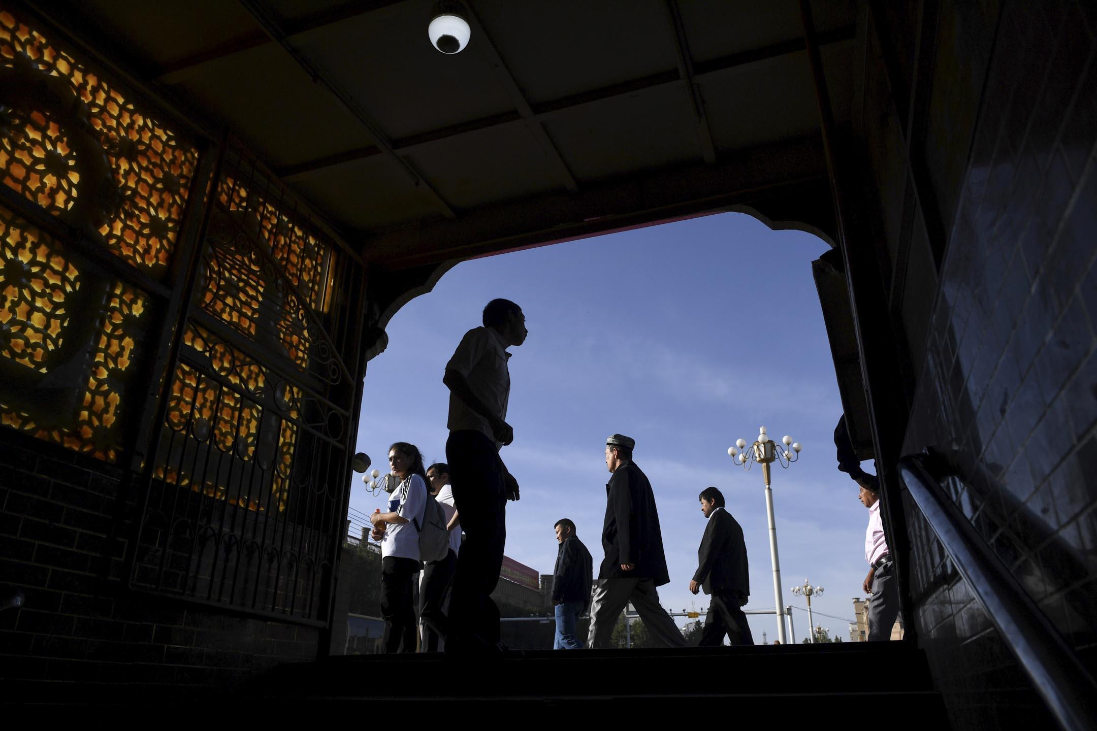 2019年6月5日,新疆,維吾爾族男子在參加開齋節的祈禱後走過地下通道的出口。 攝:Greg Baker/AFP via Getty Images