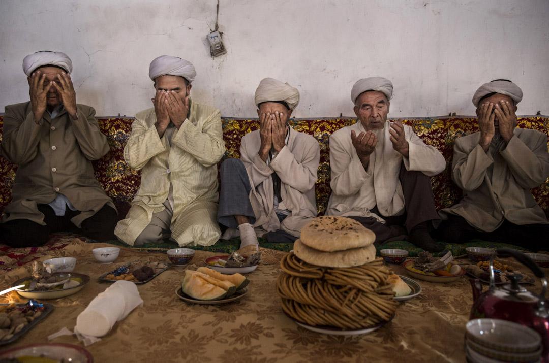 2016年9月13日,中國新疆西部的吐魯番,維吾爾族男子在吃節日大餐前祈禱。 攝:Kevin Frayer/Getty Images