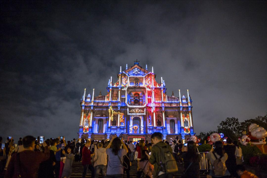 2019年12月18日,民眾在澳門大三巴牌坊欣賞澳門光影節的光雕表演。