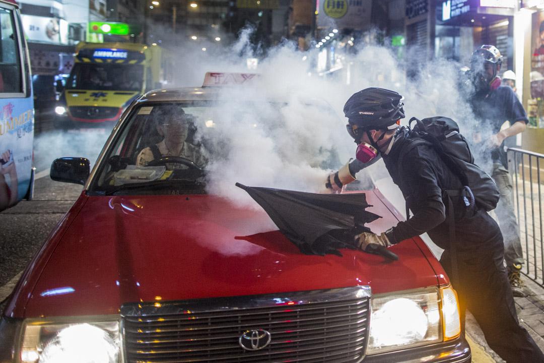 2019年9月29日,示威者拾起射到計程車上的催淚彈。