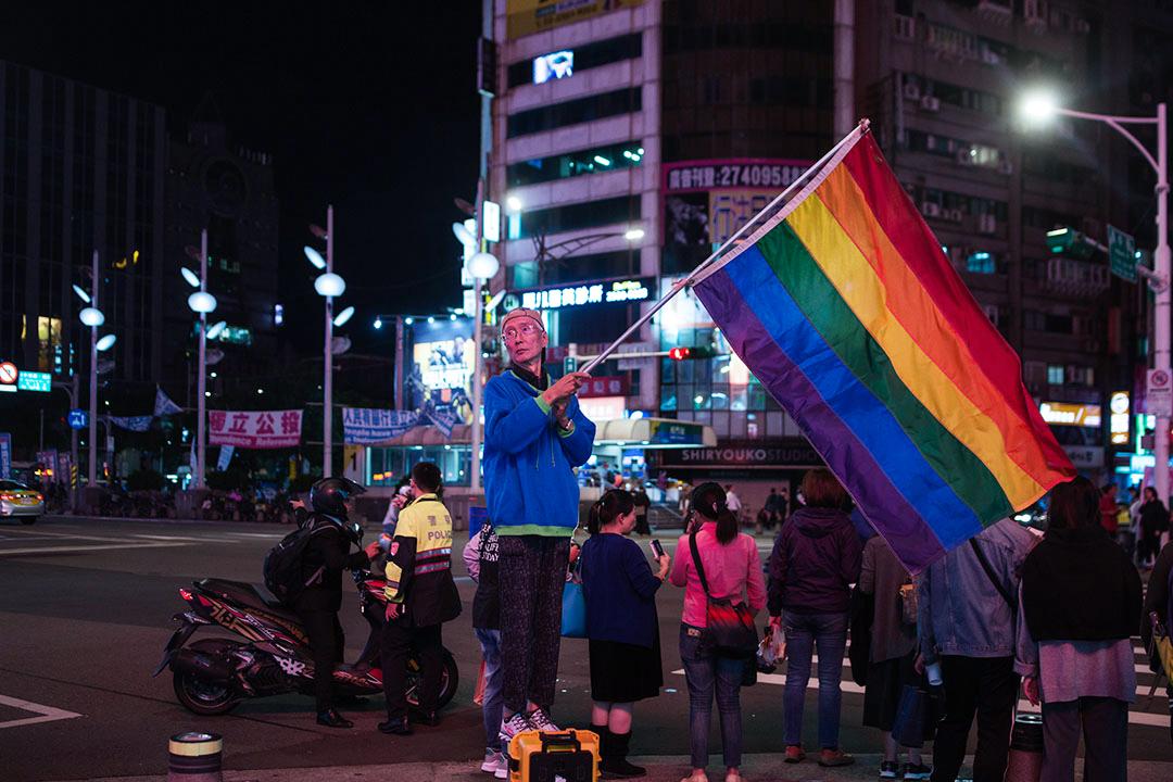 知名同運人士祁家威在公投前於台北西門町高舉彩虹旗。 攝:陳焯煇/端傳媒