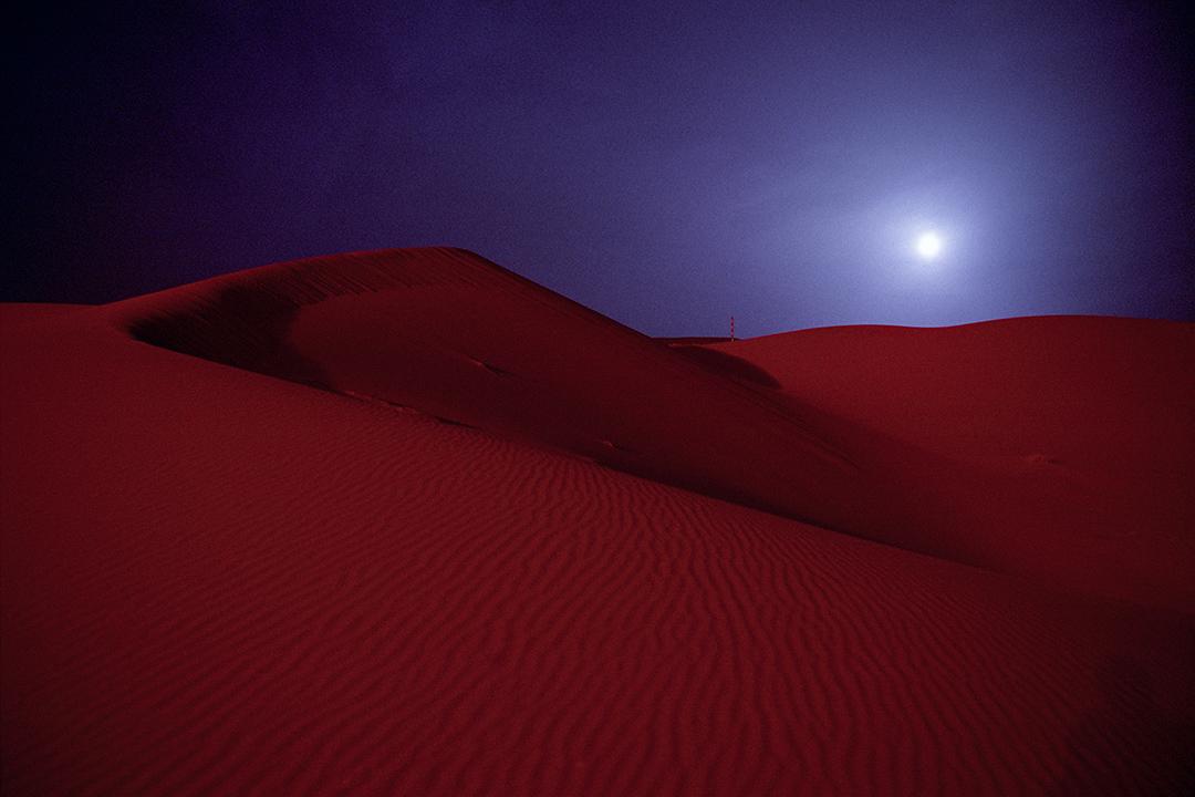 2003年3月,沙特阿拉伯油田的紅色沙丘上滿月升起。