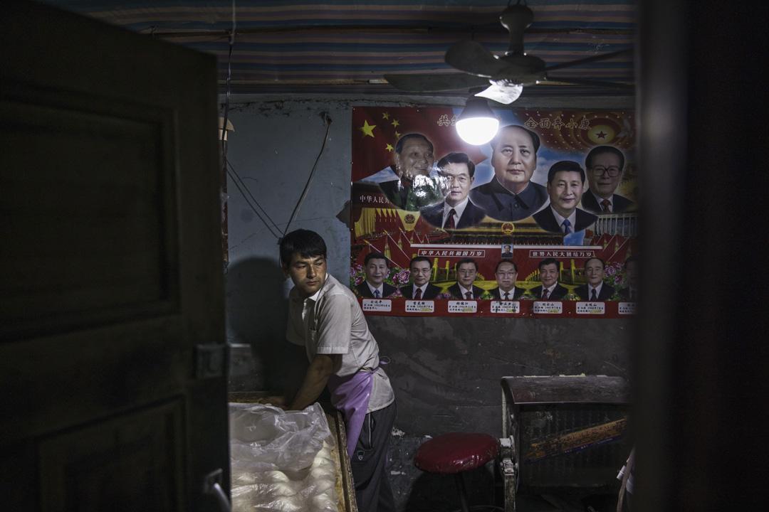 2017年7月1日,中國新疆西部喀什老城區的一家饢店,店後方有一張歷任中共領導人的海報貼在牆上。