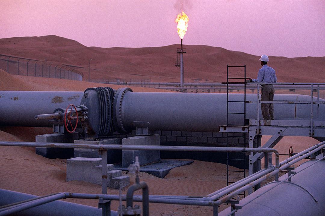 一名工人在沙特阿拉伯油田管道上。