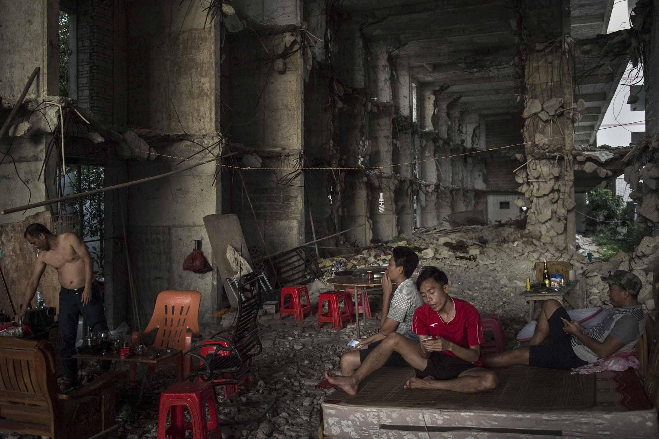 2016年10月12日,人們蹲在拆卸中的一個三亞建築物中。 攝:Nicolas Asfouri/AFP via Getty Images