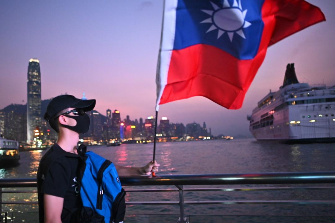 2019年10月10日,香港維多利亞港,一名黑衣男子舉起青天白日旗。 攝:Philip Fong/Getty Images