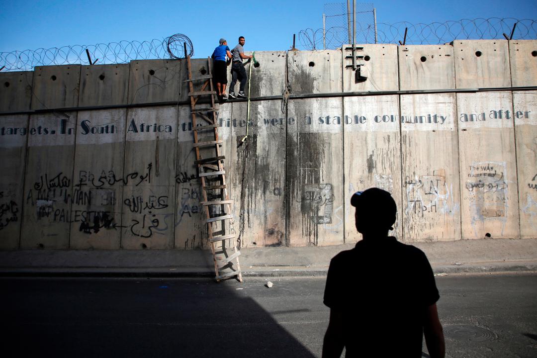 2017年6月9日,兩名巴勒斯坦青年企圖越過卡蘭迪亞的邊境,前往耶路撒冷。 攝:Abbas Momani/AFP via Getty Images