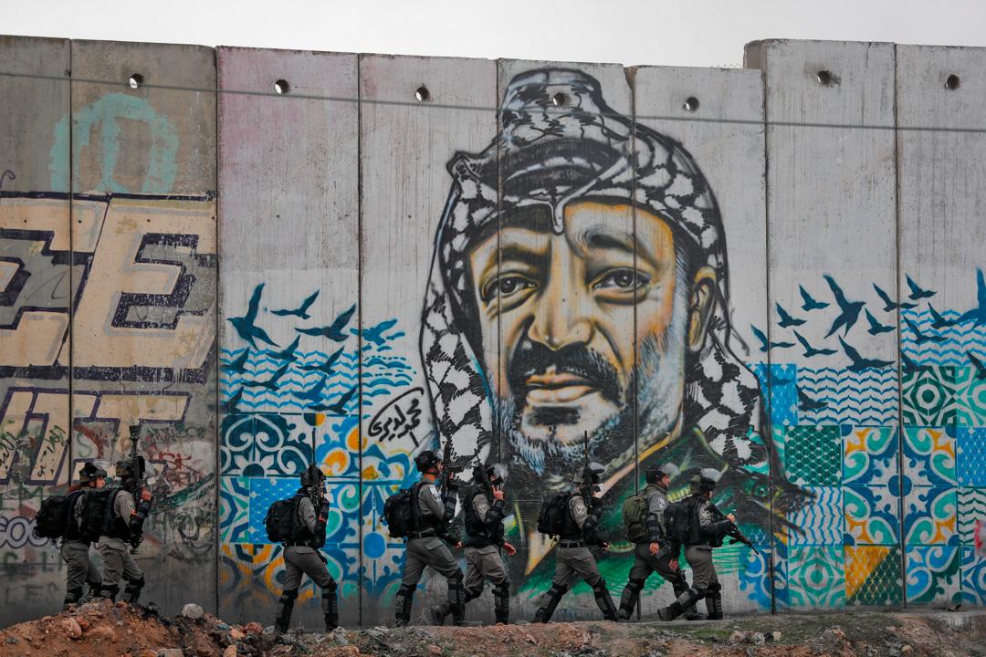 在卡蘭迪亞,以色列士兵經過巴勒斯坦解放運動領袖亞西爾·阿拉法特的巨型壁畫。