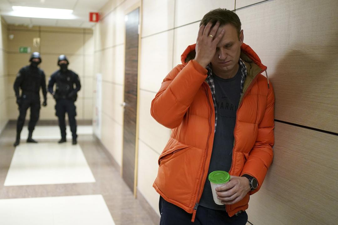 2019年12月28日,俄羅斯反對派領袖納瓦爾尼(Alexei Navalny)的辦公室遭蒙面警員破門闖入搜查,納瓦爾尼被勒令離開現場。圖為納瓦爾尼在辦公室外走廊等候,其背後有兩名警員駐守。 攝:Dimitar Dilkoff / AFP via Getty Images