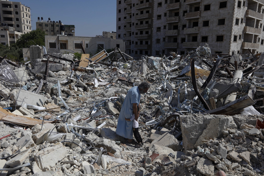拉姆安拉的難民營裡,被以色列官方拆毀的建築物中,一名巴勒斯達男子與小孩相擁。