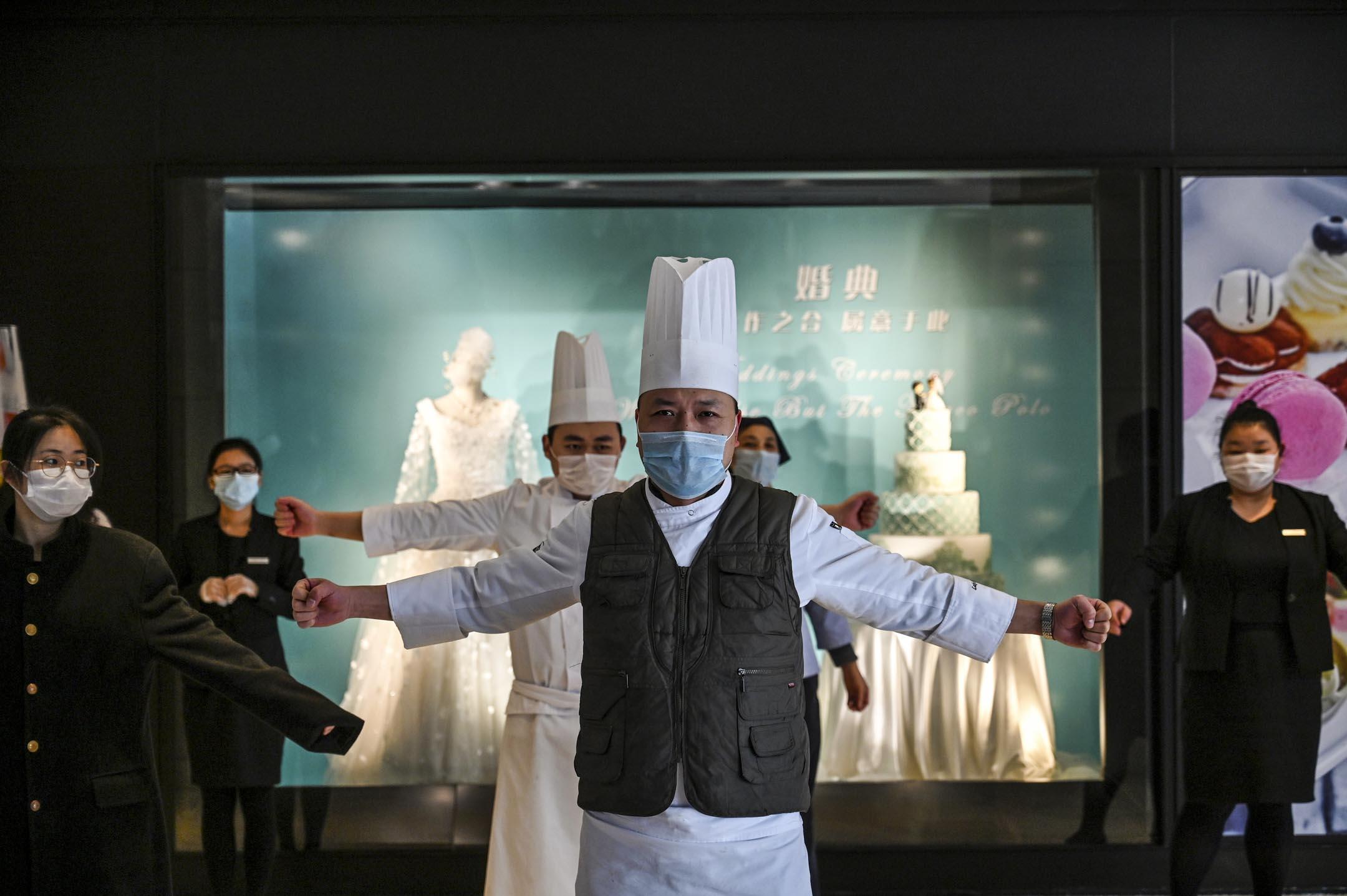 2020年1月28日,在武漢肺炎爆發期間,武漢一間酒店的工作人員在大廳裡鍛煉身體。 攝:Hector Retamal/AFP via Getty Images