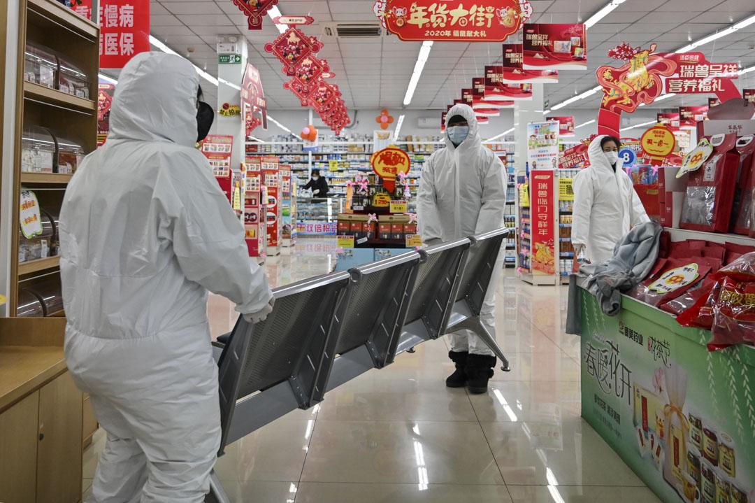 2020年1月25日,戴著防護服和口罩的藥房工作人員在武漢為顧客服務。