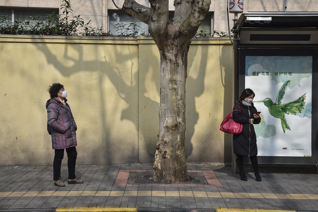2020年1月21日在中國上海復旦大學附屬華山醫院外的一個巴士站,兩名女士分別戴着口罩等候巴士。 攝:Hector Retamal / AFP via Getty Images
