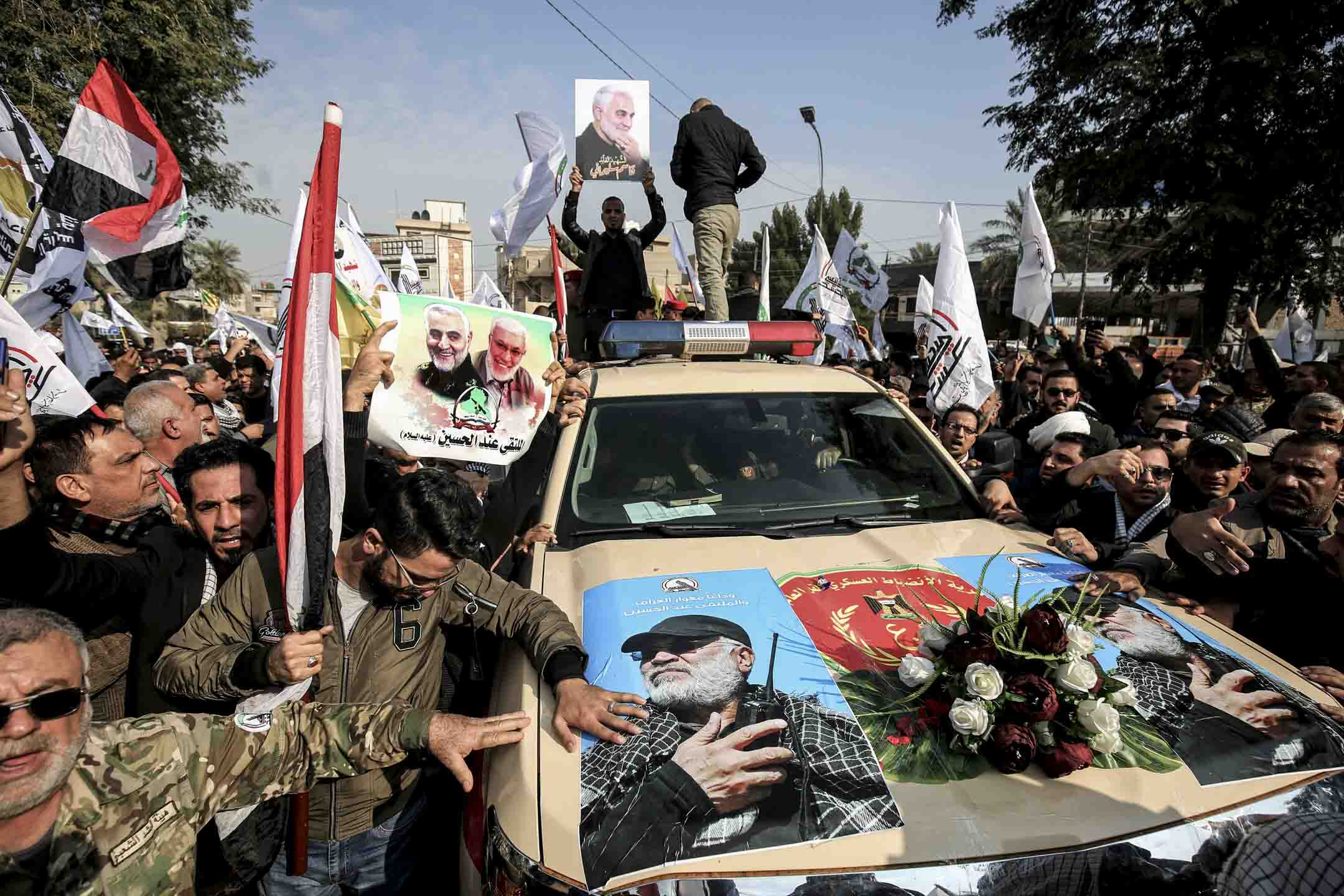 2020年1月4日,伊朗革命衛隊聖城軍指揮官蘇萊曼尼(Qassem Soleimani)的葬禮,送葬者在隊伍中圍著一輛載有遺體棺木的汽車。 攝: Ahmad Al-Rubaye/AFP via Getty Images