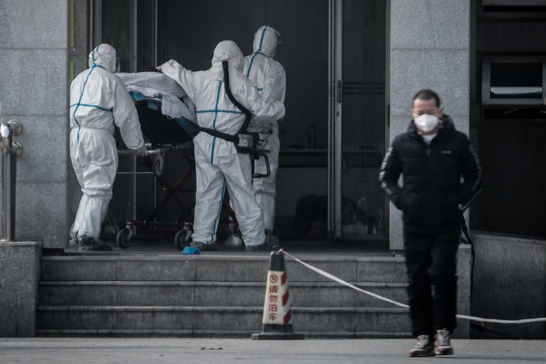 2020年1月18日,醫護人員將一名病患者送至武漢市金銀潭醫院。 攝:STR/AFP via Getty Images