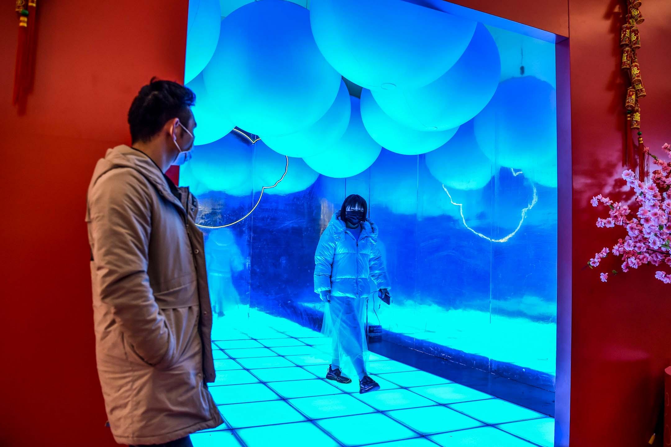 2020年1月23日,武漢一家購物中心內,顧客們都戴上了口罩。 攝:Hector Retamal/AFP via Getty Images
