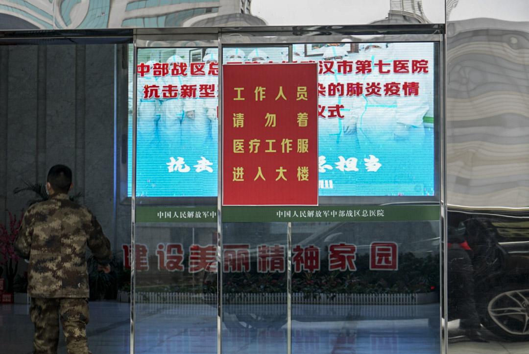 2020年1月26日,武漢市中部戰區總醫院醫護人員從志願者處領取物資。