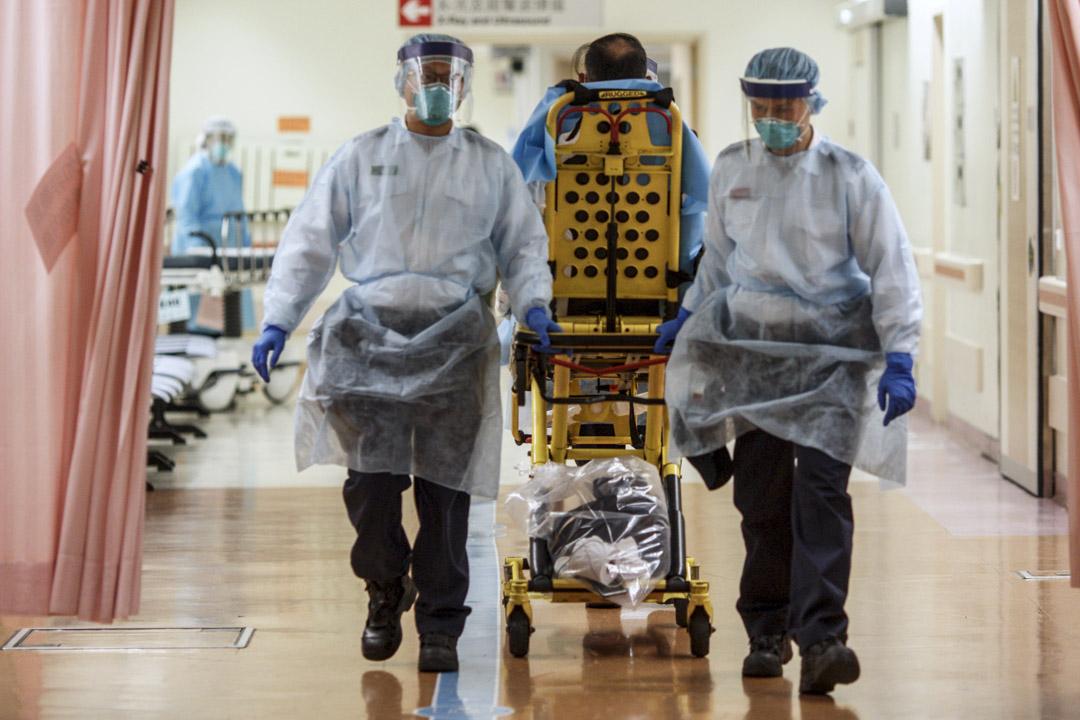 2020年1月22日,香港威爾斯醫院一名病人對新冠狀病毒初步呈陽性反應,由醫院人員協助離開並送去瑪嘉烈醫院。 攝:陳焯煇/端傳媒