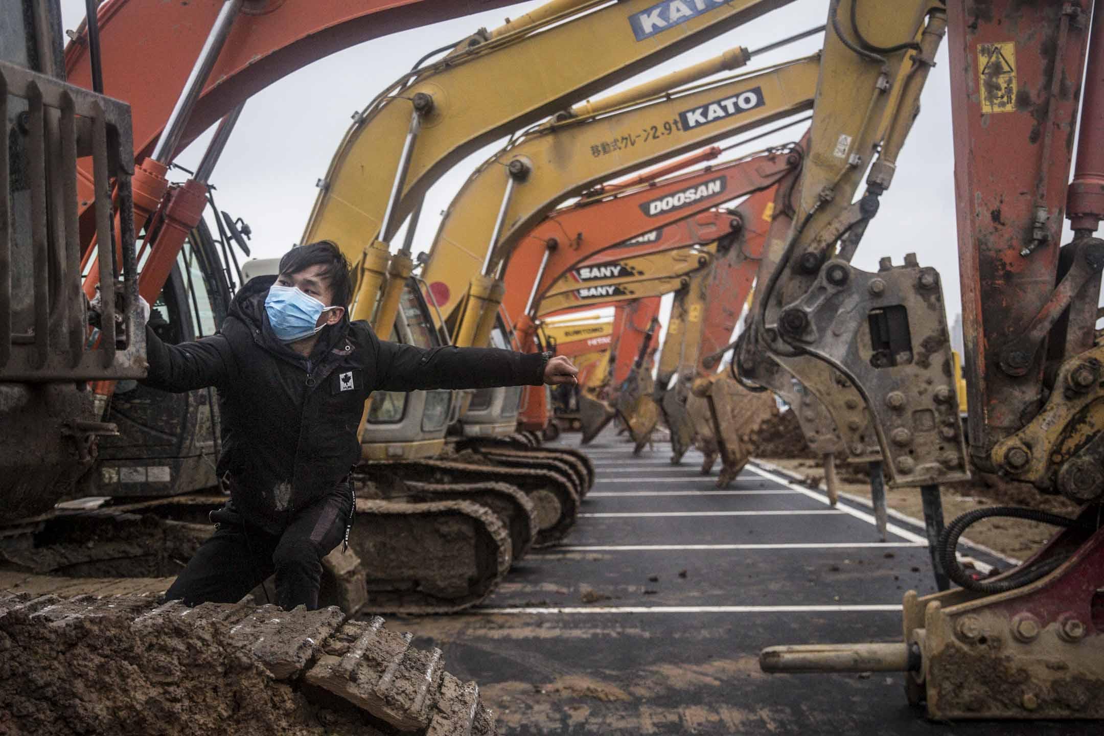 2020年1月26日,武漢一名司機在醫院的施工現場。武漢政府正在興建可容納1000個床位的新醫院,以應付新型冠狀病毒的醫療需求。醫院計劃於2月3日建成。