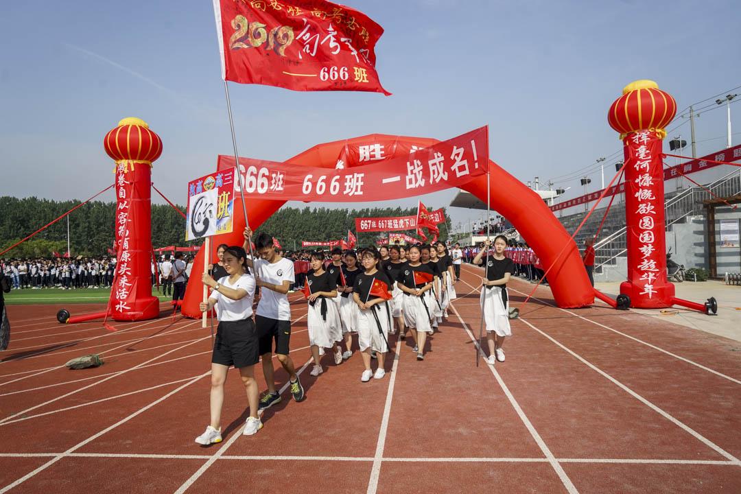 河南一間高中的學生在畢業典禮的操場上高舉「2019年全國高考」的成功標語。 攝:Wang Xiangyang/Visual China Group via Getty Images