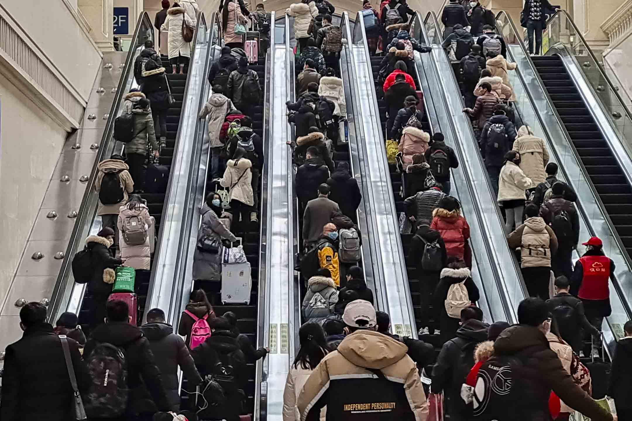 2020年1月22日,中國武漢的漢口火車站內,自動扶手電梯上,不少旅客都戴上口罩。