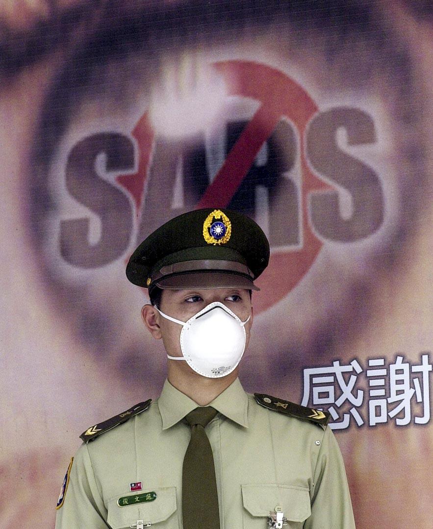 2003年台北,一名軍裝警員在醫院門前戴上口罩。