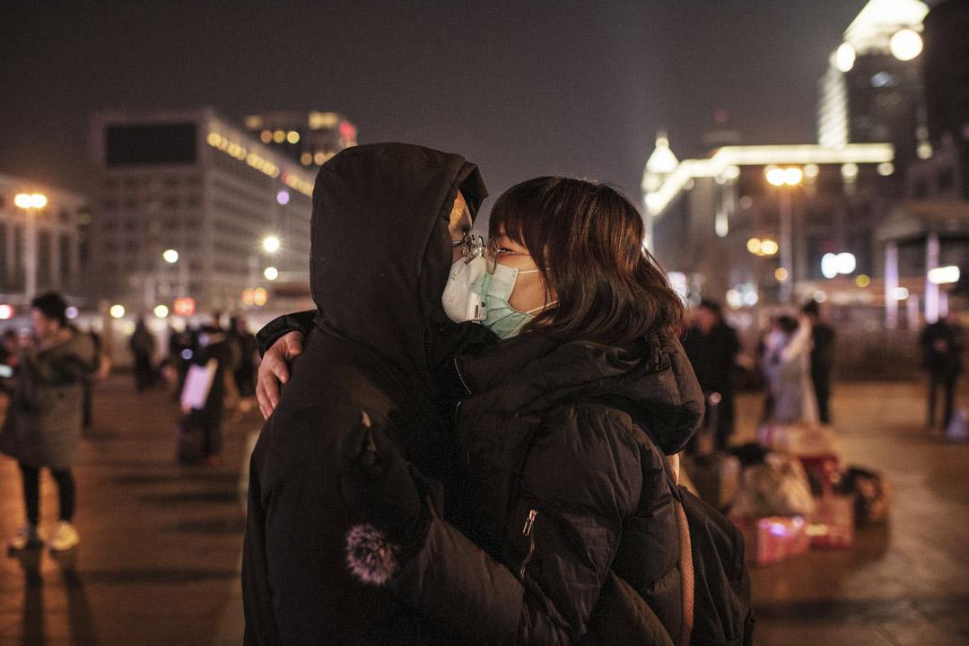 2020年1月22日,北京一對情侶隔著口罩親吻。 攝:Kevin Frayer/Getty Images