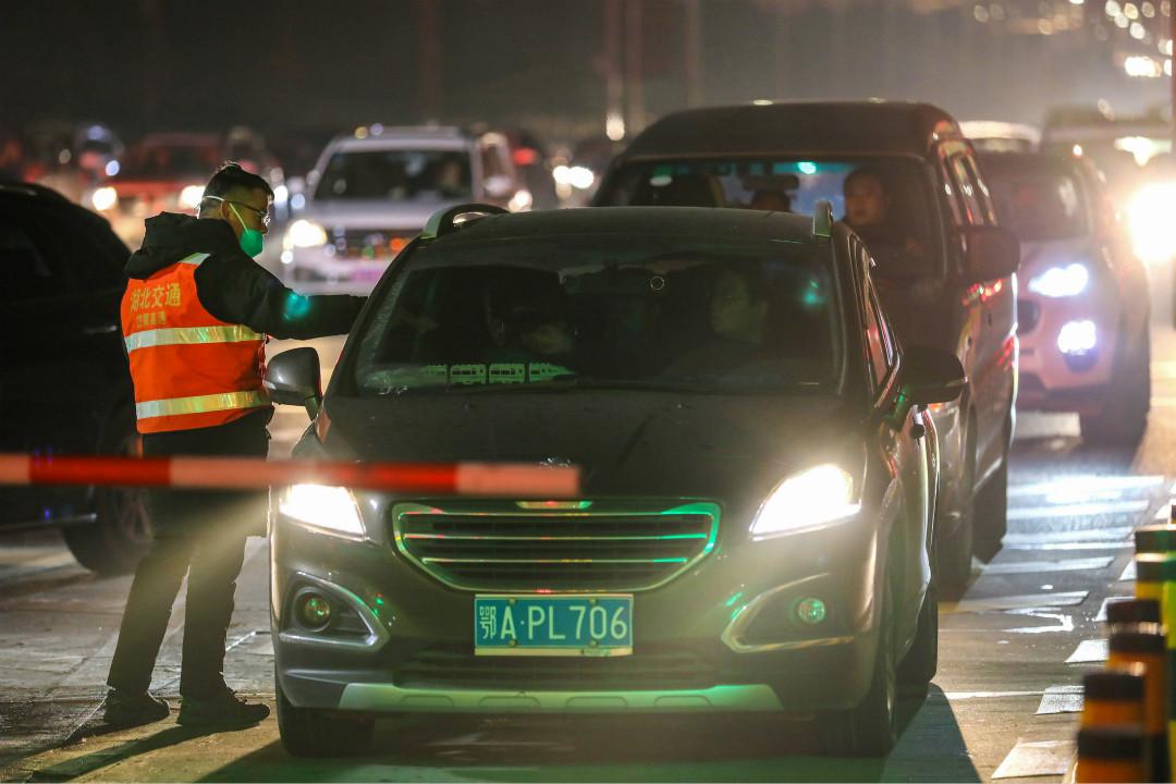 2020年1月21日,武漢高速公路,工作人員檢查過往人員體溫。 攝:Getty Images