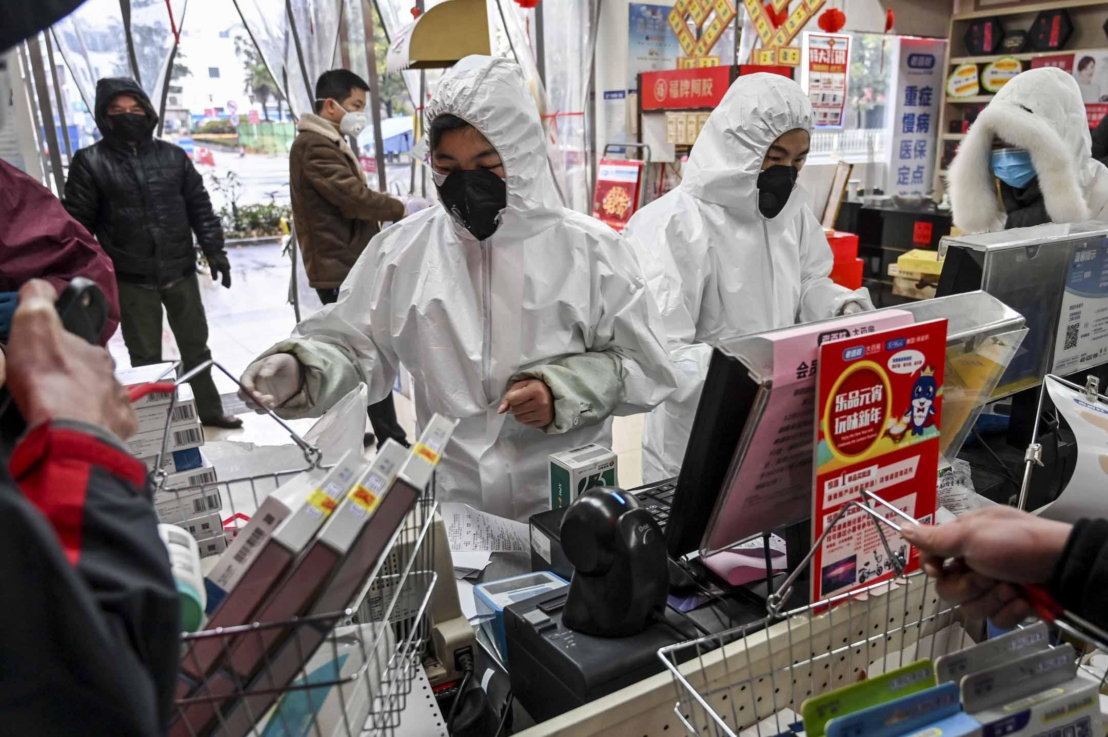 2020年1月25日,戴著防護服和口罩的藥房工作人員在武漢為顧客服務。 攝:Hector Retamal/AFP via Getty Images