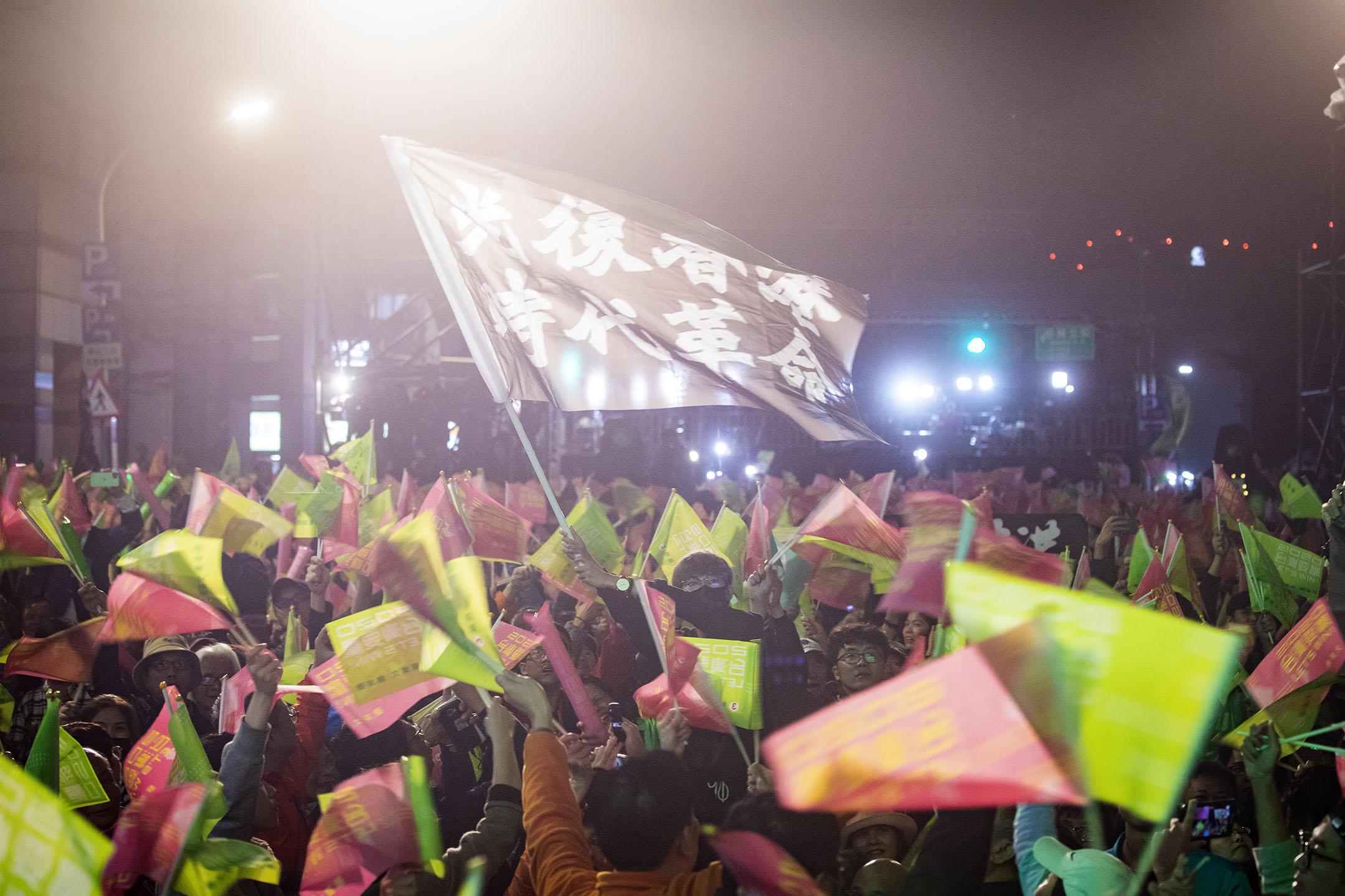 2020年1月11日台北,民進黨的開票晚會上,一名參與者高舉「光復香港時代革命」的旗幟。