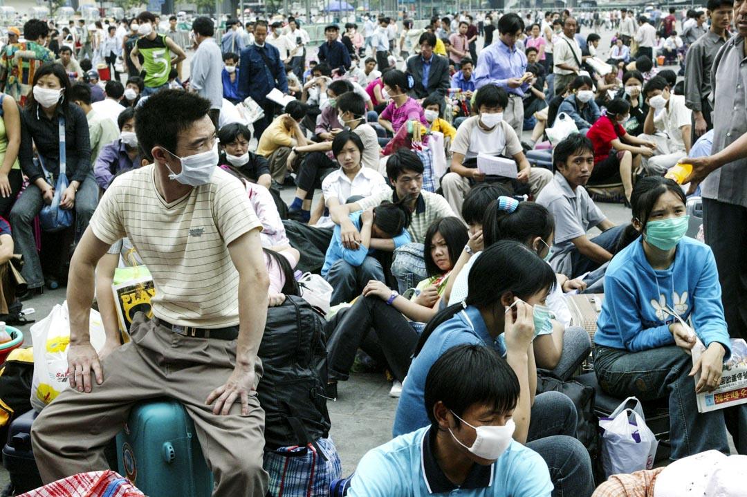 2003年5月2日,廣州市發生SARS疫情期間,農民工在火車站外等著回家。