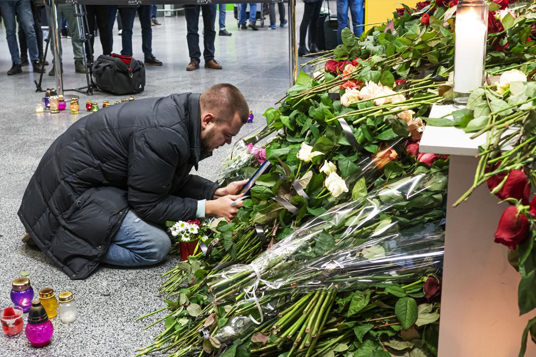 2020年1月9日在烏克蘭首都基輔的鮑里斯波爾國際機場,民眾以鮮花悼念客機墜毁事件的死難者。一名男子雙膝跪地、親吻一幀死難者遺照,據報他是其中一名罹難空中服務員的丈夫。 攝:Igor Golovniov / Getty Images