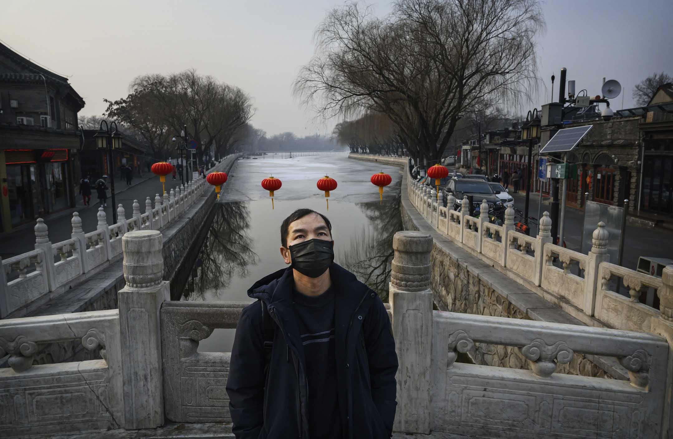 2020年1月26日,春節期間,一名男子站在后海的一座橋上戴著防護口罩。