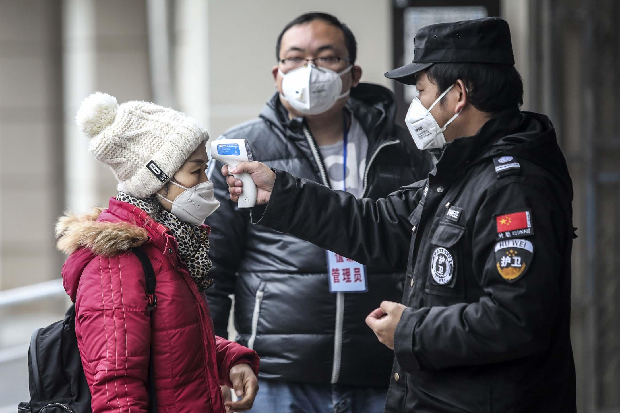 2020年1月22日,武漢市安全人員檢查長江碼頭乘客的體溫是否正常。