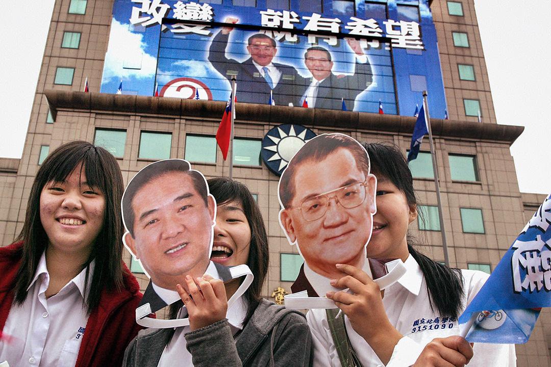 2004年3月19日,女孩在台北國民黨總部前舉起台灣總統候選人連戰和副總統候選人宋楚瑜的面具。