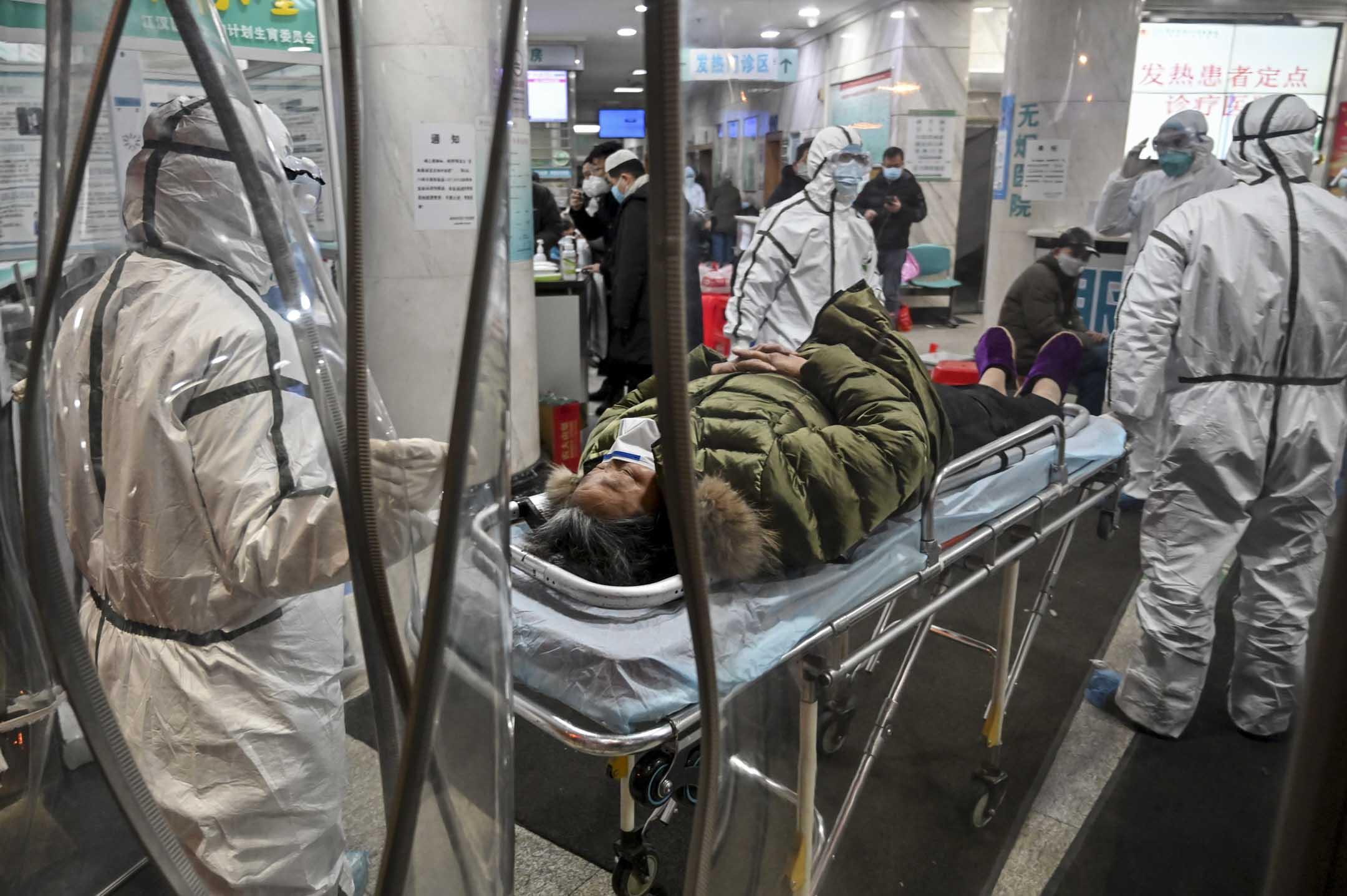 2020年1月25日,一名病人到達武漢市紅十字會醫院,由穿上防護衣的醫務人員帶進醫院。