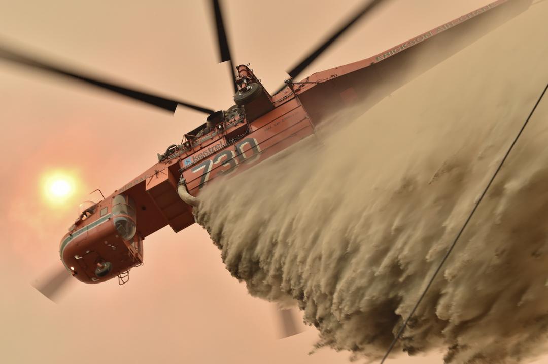 2019年12月9日,澳洲悉尼西南方的郊區,一台直升機正在撒下阻燃劑嘗試阻止火勢。